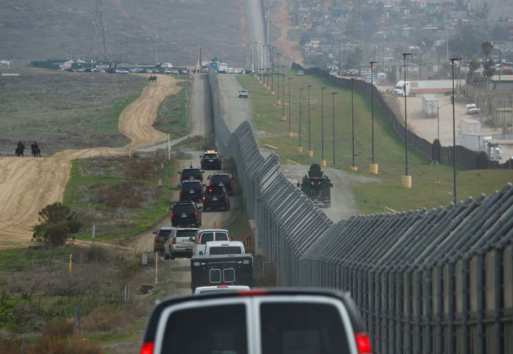 Border Patrol agent Eduardo Olmos walks near the secondary fence separating Tijuana, Mexico, background, and San Diego in San Diego. (AP).