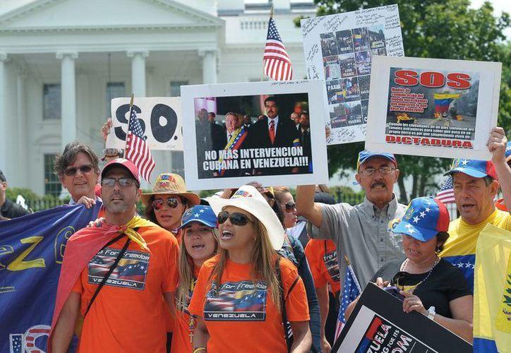 """Los manifestantes cantaron el himno nacional """"Gloria al pueblo"""" antes de partir hacia la OEA. (EFE)"""