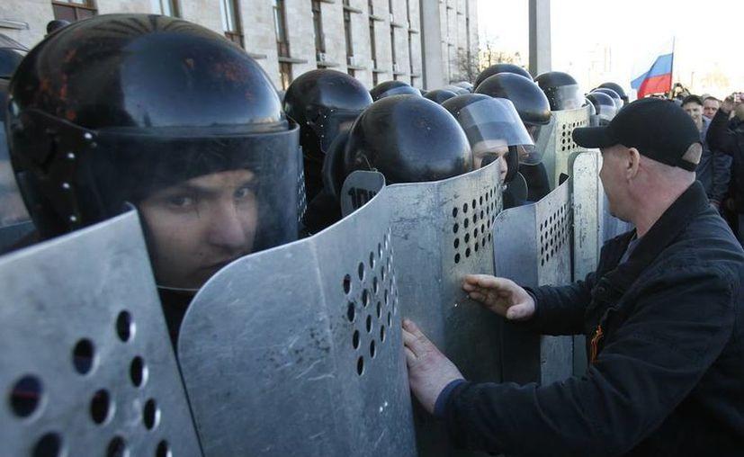 Activistas prorrusos se enfrentan a la policía que bloquea la entrada a la oficina regional del Gobierno, durante una manifestación en Donetsk. Los manifestante piden un plebiscito para determinar su eventual anexión a Rusia. (Agencias)