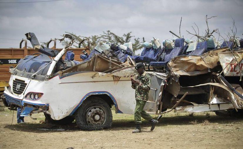 Un policía pasa junto a un autobús destruido tras un accidente de tráfico en los terrenos de una comisaría de policía en la localidad de Ntulele. (Archivo/EFE)