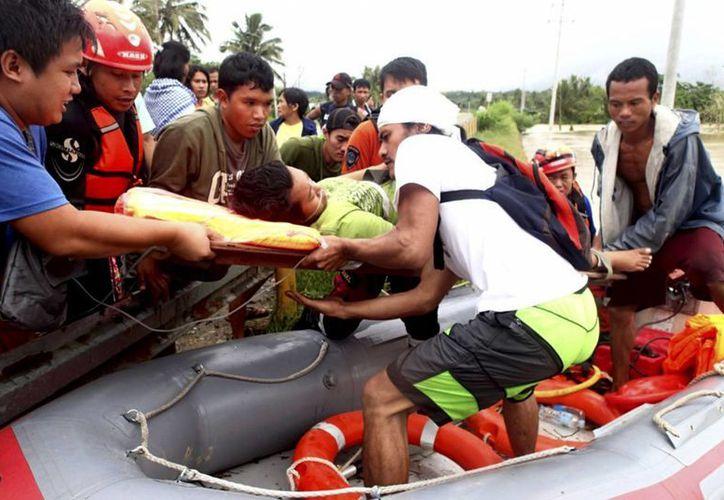 Rescatistas del grupo de respuesta a emergencias evacuan a residentes del valle de Compostela y provincias cercanas en el sur de Filipinas. (Agencias)
