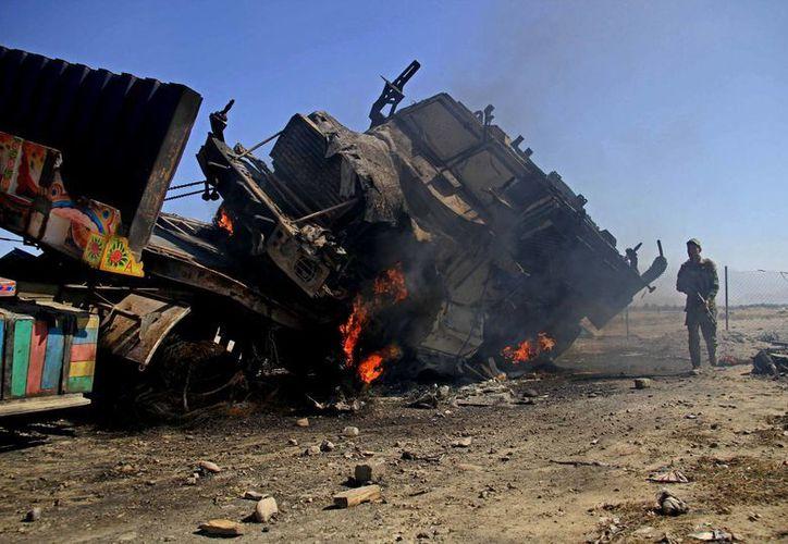 Un policía afgano se coloca cerca de uno de los camiones que suministró la OTAN, y el cual fue destruido. (Agencias)