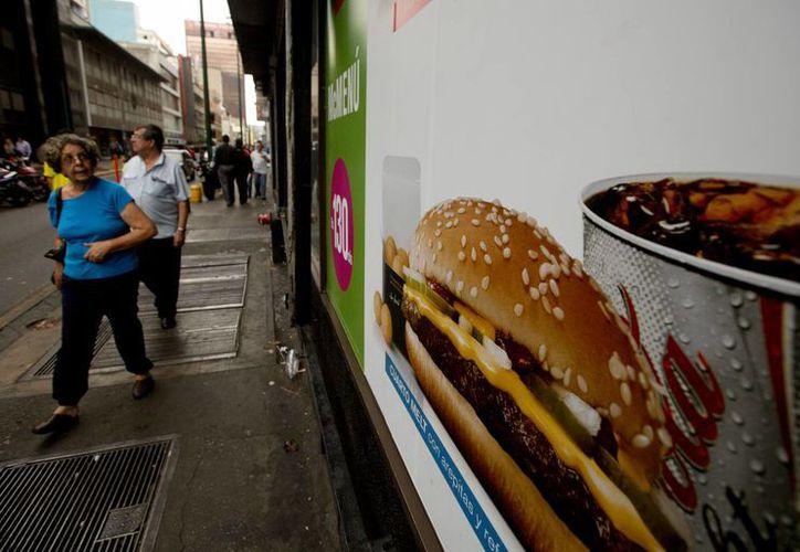 Una mujer echa un vistazo al menú de McDonalds en una vitrina, que muestra una hamburguesa acompañada de arepas en vez de papas fritas, en Caracas, Venezuela. (Agencias)
