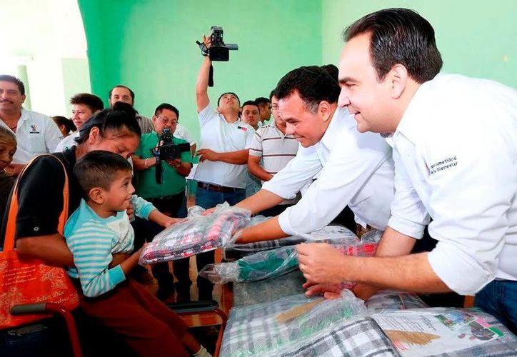 El Gobierno estatal otorgará 150 mil cobertores en mas de 106 municipios de Yucatán. Imagen del Gobernador quien entrega una cobija a un niño beneficiado. (Milenio Novedades)
