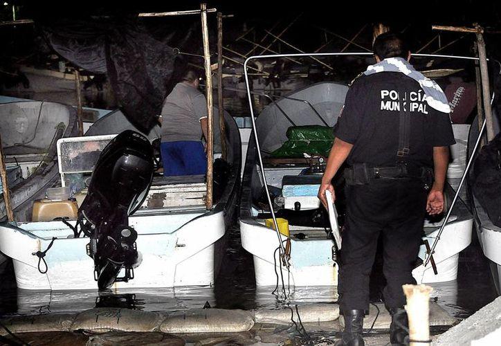 Se reportó en Sisal el fallecimiento de un pescador luego de sufrir una descompresión. Imagen de agentes de la policía al revisar la embarcación donde se encontraban los hombres de mar. (Milenio Novedades)