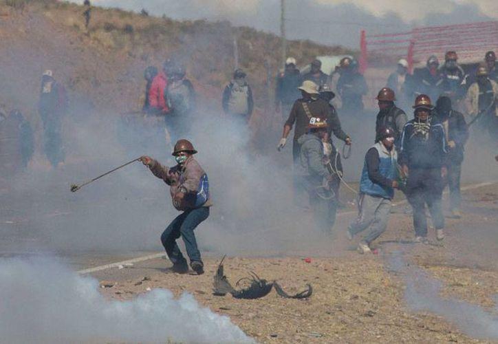 Mineros independientes chocan con la policía mientras huyen de gases lacrimógenos durante protestas en Panduro, Bolivia, el jueves 25 de agosto de 2016. (AP Foto/Juan Karita)