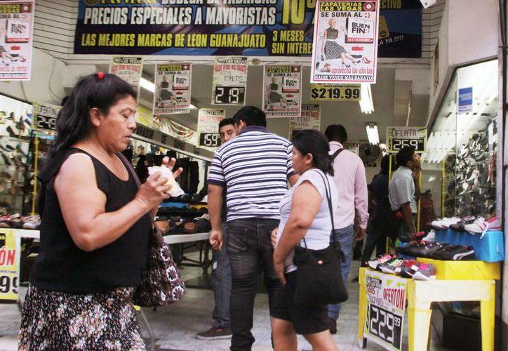 No se reportaron mayores incidencias durante la jornada de El Buen Fin. En la imagen, una mujer pasa en las puertas d eun comercio en el Centro de Mérida.(Milenio Novedades)