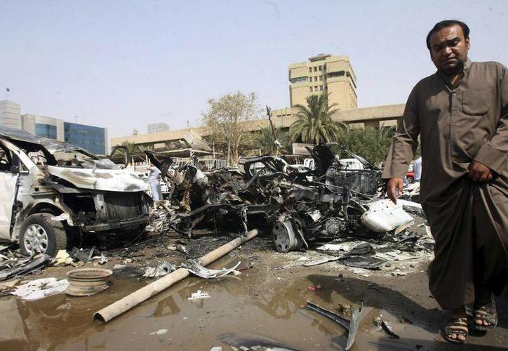 Un civil pasa por delante de un concesionario donde fue perpetrado un ataque con bomba, en el distrito Nahda, en Bagdag, Irak. (Archivo/EFE)