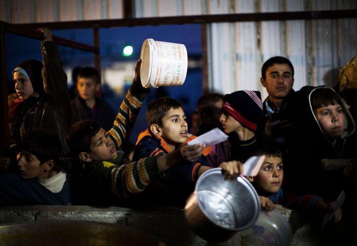 Niños sirios en espera de comida en un refugio en la frontera con Turquía. (Agencias)