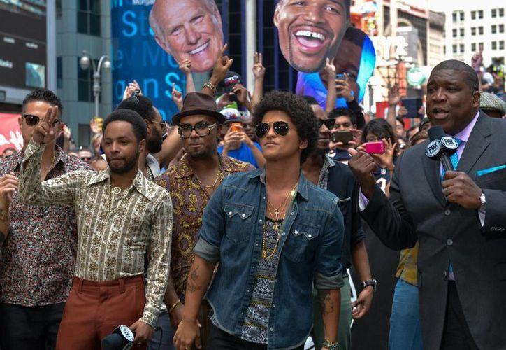 El cantante y compositor Bruno Mars (lentes oscuros) dará su toque particular al Super Bowl. (Agencias)