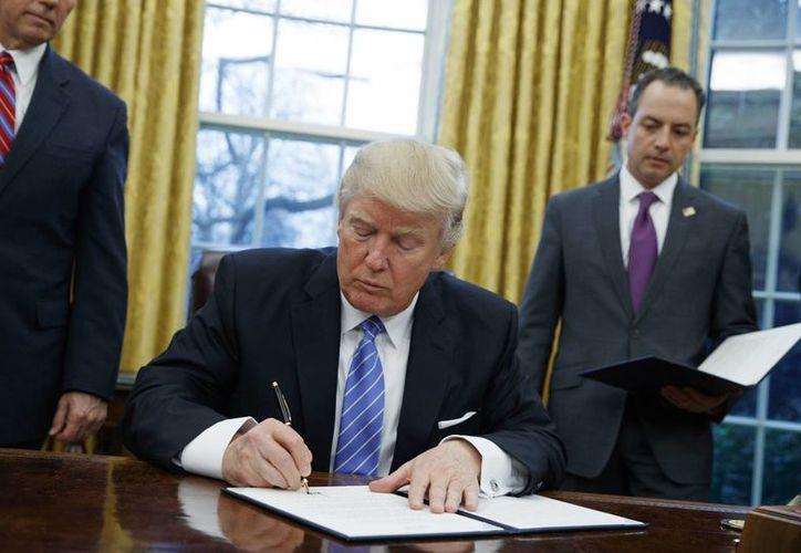 Donald Trump firmó el lunes 23 de enero de 2017, un decreto mediante el cual EU se retira del Acuerdo Transpacífico. (AP/Evan Vucci)