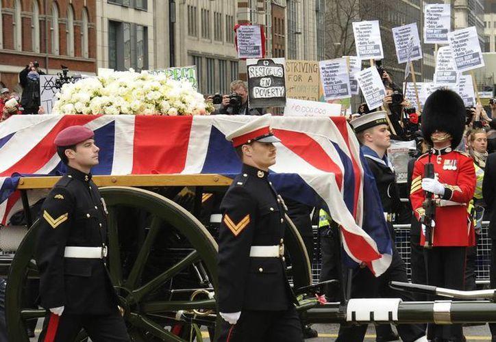 El ataúd, cubierto con la bandera británica y un ramo de rosas blancas, es transportado en un armón de artillería tirado por seis caballos y escoltado por miembros de las tres fuerzas armadas. (EFE)