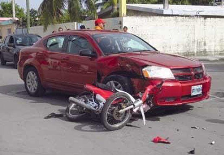 El auto rojo y la motocicleta terminaron con severos daños materiales, luego del fuerte impacto, ayer en Cozumel. (Redacción/SIPSE)