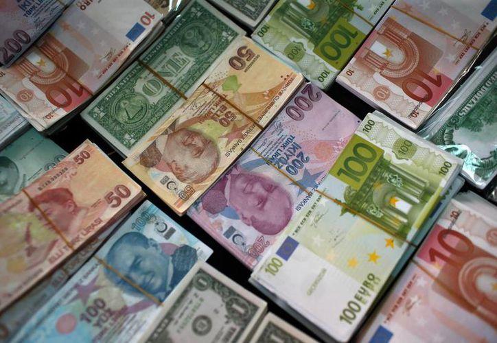 Fajos de billetes de liras turcas, euros y dólares en una oficina cambiaria en Estambul, Turquía. Las monedas de mercados económicos emergentes se han devaluado alrededor del mundo. (Agencias)