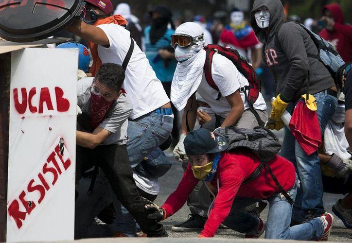 Manifestantes opositores al enfrentarse a miembros de la Policía Nacional Bolivariana (PNB), tras una concentración convocada por las organizaciones opositoras estudiantiles, en Caracas. (EFE)
