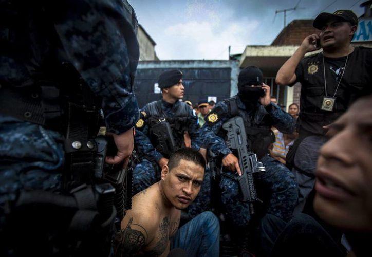 """Agentes de la Policia escoltan a William Lázaro, alias """"el Escandaloso"""", supuesto pandillero de la Mara 18, en una zona de alto riesgo de la ciudad de Guatemala. (EFE)"""