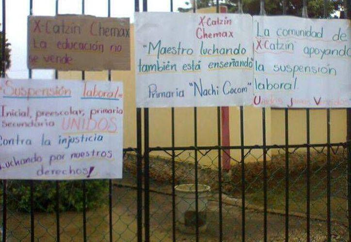 Carteles de protesta en una escuela de Chemax. (SIPSE)