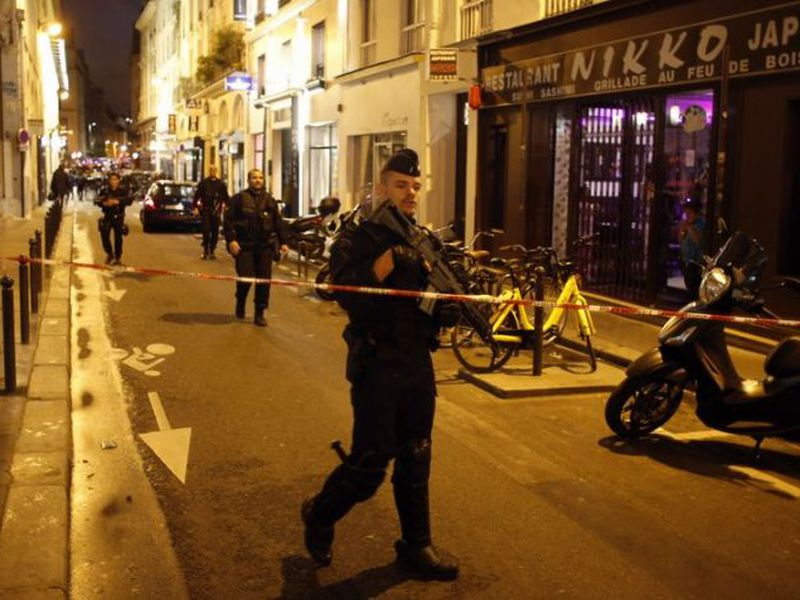 Police officers secure the area after a knife attack in central Paris.