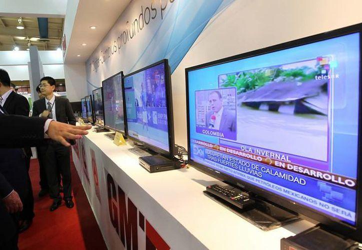 Varias personas observan una emisión de televisión digital en el stand de una compañía china que participa en la XV Convención y Feria Internacional Informática 2013. (EFE)