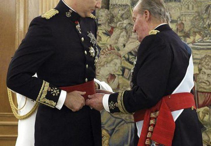 Juan Carlos de Borbón coloca a Felipe VI el fajín que lo reconoce como capitán de los tres ejércitos de España. (AP)