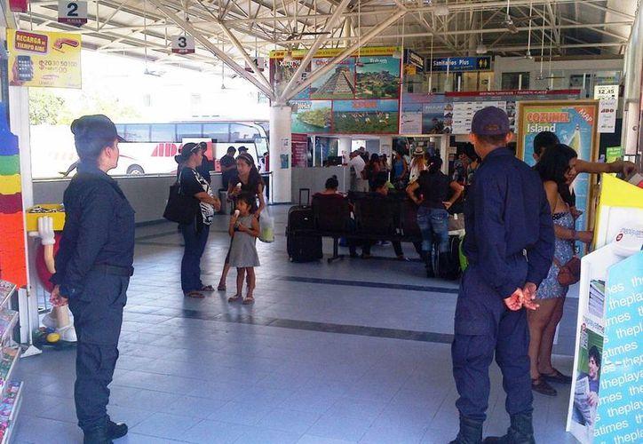Elementos de la Policía Federal resguardan y emiten recomendaciones a los viajeros que llegan por autobús a Playa del Carmen.  (Daniel Pacheco/SIPSE)