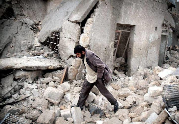 Un hombre sirio camina en medio de escombros en el barrio Jabal Badero después de un supuesto ataque con misiles dos días atrás en Alepo, Siria. (EFE)