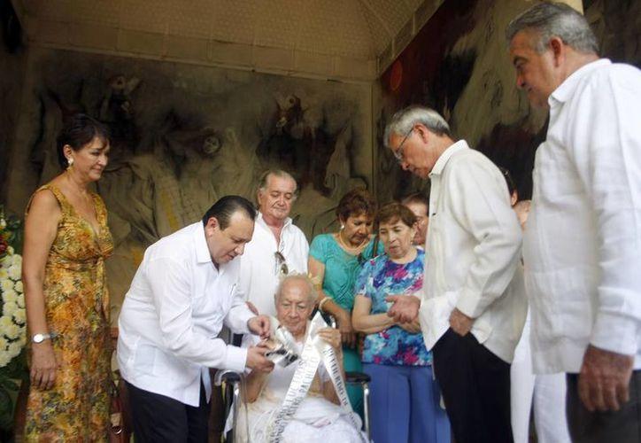En presencia de Blanca Sol Sumohano, viuda del pintor, autoridades realizan una ofrenda floral. (Christian Ayala/SIPSE)