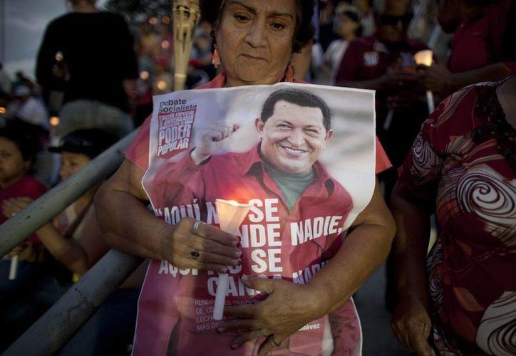 Una mujer sostiene una vela junto a un cartel del presidente de Venezuela, Hugo Chávez, durante una vigilia con velas para rezar por su salud. (Agencias)