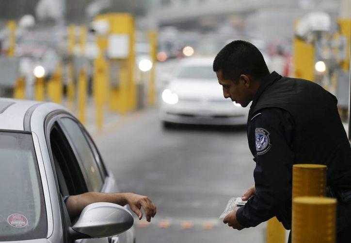 Un guardia entrevista a un conductor de un vehículo en el puesto fronterizo de San Ysidro, en San Diego. (Agencias)