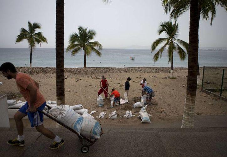 Los habitantes de Puerto Vallarta preparan costales de arena para impedir el avance de las olas que causa el huracán Patricia en las costas de Jalisco. (AP)