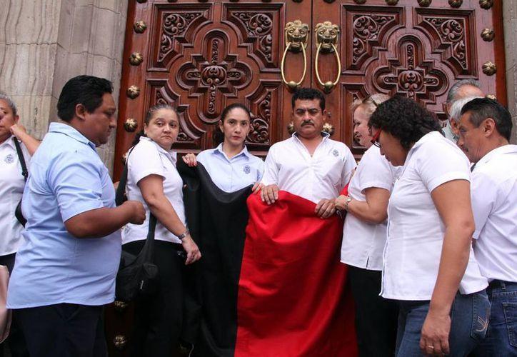Momento en que trabajadores de la Uady colocaron la bandera rojinegra en las puertas de la institución universitaria. (José Acosta/SIPSE)