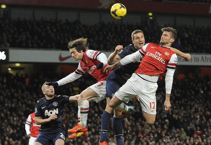 El defensa del Manchester United, Nemanja Vidic (2d), ante Olivier Giroud (d) del Arsenal durante el juego de la Liga Premier. (EFE)