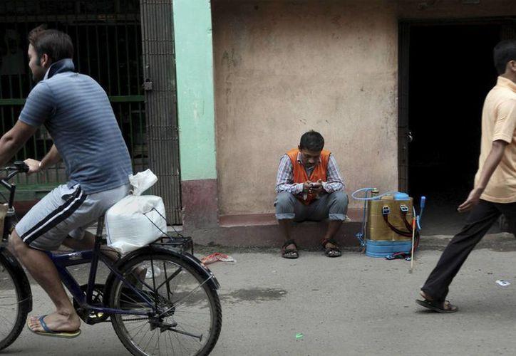 Un funcionario descansa tras fumigar con pesticida para eliminar el mosquito causante de la malaria en Calcuta, India. (Archivo/EFE)