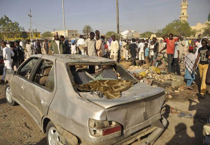 La gente se reúne en el lugar de la explosión de una bomba en Kano, Nigeria. (Agencias)