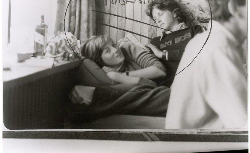En la foto se ve a Diana reclinada en una cama junto a un joven sentado detrás de ella y una botella de whisky. (Agencias)
