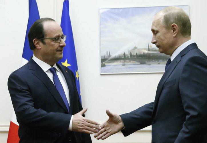 El presidente ruso, Vladimir Putin (der), se acerca a darle la mano a su homólogo francés, Francois Hollande durante su encuentro en el aeropuerto Vnukovo de Moscú. (Agencias)