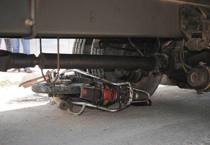 La moto en la que viajaban 4 personas, tres niñas como pasajeras, quedó debajo del camión que la embistió. Una de las niñas murió en el hospital, cuando recibía atención médica. (