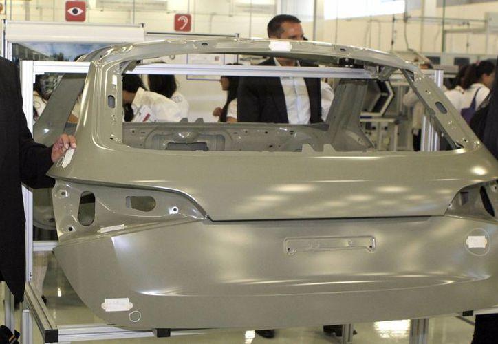 La producción de vehículos ligeros en México registró en agosto un récord histórico, tanto para el mes como para el acumulado. Imagen del ensamblaje de un vehículo nuevo. (Archivo/Notimex)