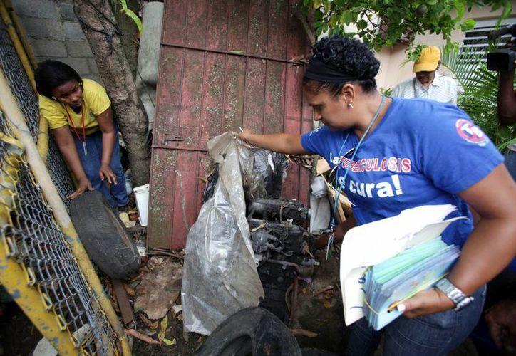 Voluntarias revisan una vivienda donde hay agua acumulada, la cual genera nidos del virus del chikungunya. (Archivo/EFE)