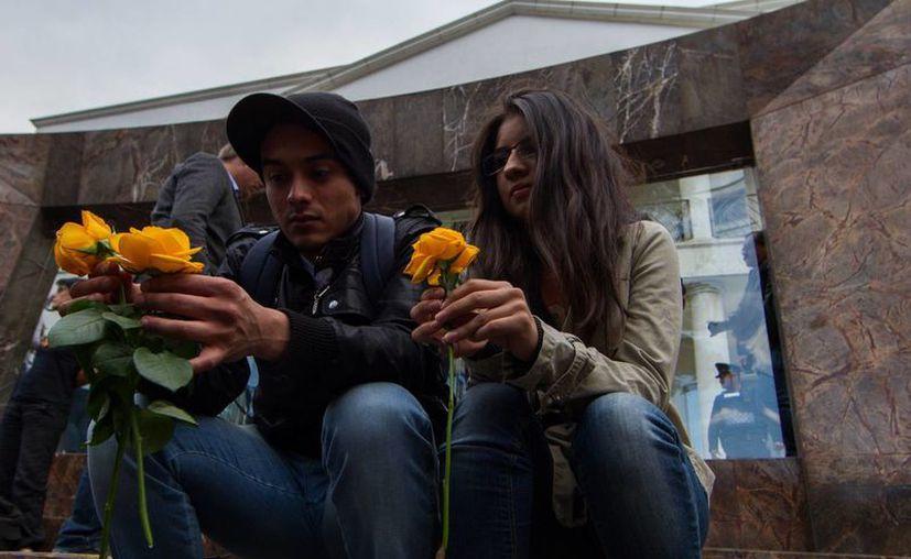 Dos jóvenes esperan en la funeraria con rosas amarillas en las manos, las favoritas del escritor colombiano Gabriel García Márquez. (Notimex)