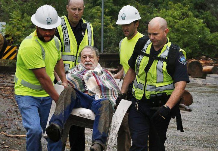 Un hombre es rescatado por los trabajadores de emergencia después de quedar atrapado en un refugio. (Agencias)
