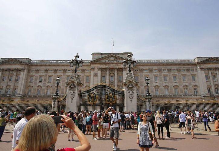 Un grupo de personas aguarda en la entrada del palacio de Buckingham, en Londres. (Archivo/EFE)