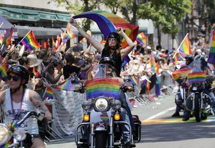 Una mujer en una motocicleta ondea la bandera LGBT durante el Desfile del Orgullo Gay en Nueva York. (EFE)