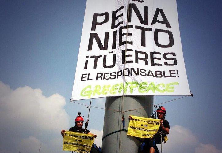 Activistas de Greenpeace se subieron casi hasta arriba del astabandera para colocar su petición. (twitter.com)