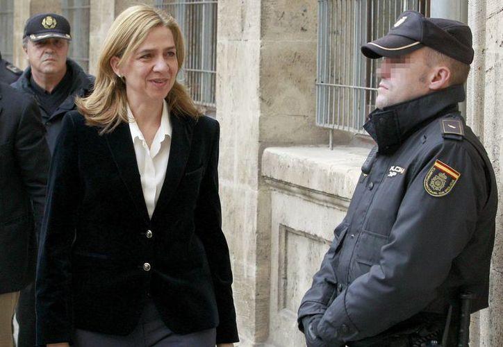 Tanto a su entrada como a la salida, doña Cristina se mostró sonriente y saludó a los medios de comunicación. (EFE)