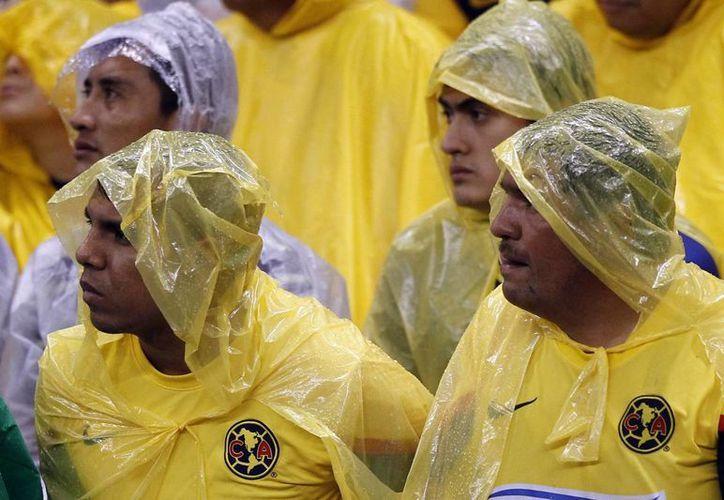 La lluvia no mermó el ánimo de los aficionados. (Notimex)