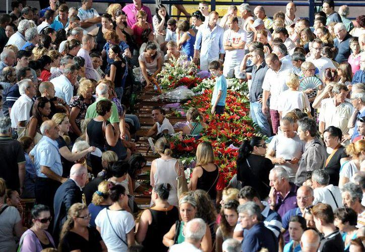 Familiares lloran la pérdida de sus seres queridos sobre los ataúdes. (EFE)
