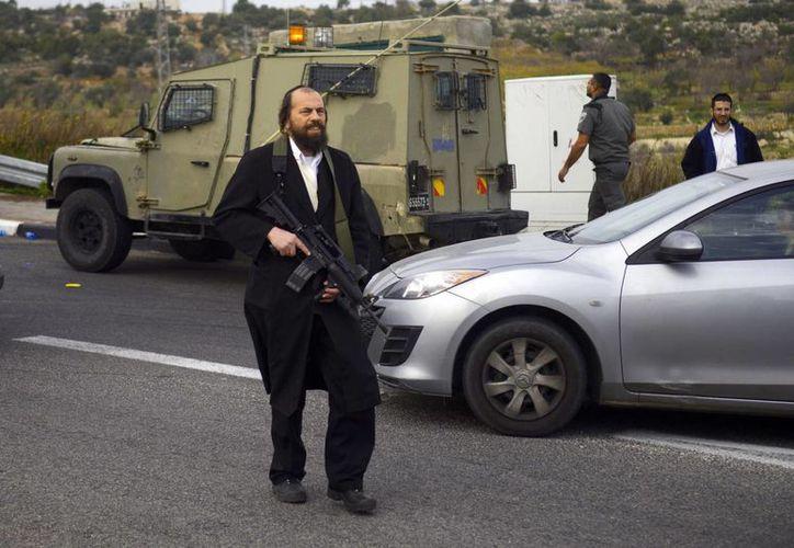 Un ultraortodoxo judio camina en la escena donde ocurrió el ataque con ácido contra una familia, cerca del asentamiento de Gush Etzion en Cisjordania. (Agencias)