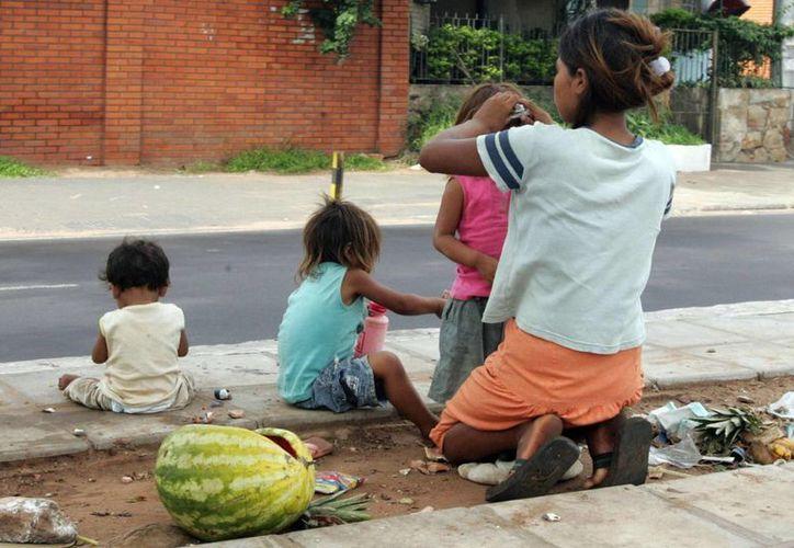 Una mujer que podría sufrir carencias alimenticias y extrema pobreza cuida a sus hijos en una calle del país.  (EFE)