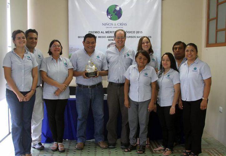 La agrupación Niños y Crías A.C. posan con el premio nacional que obtuvieron por sus trabajos de conservación ambientalistas. (César González/SIPSE)